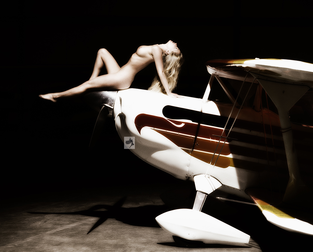 Photograph of nude woman on vintage biplane. Portrait by Mark Laurie of Inner Spirit Photography studio Calgary.